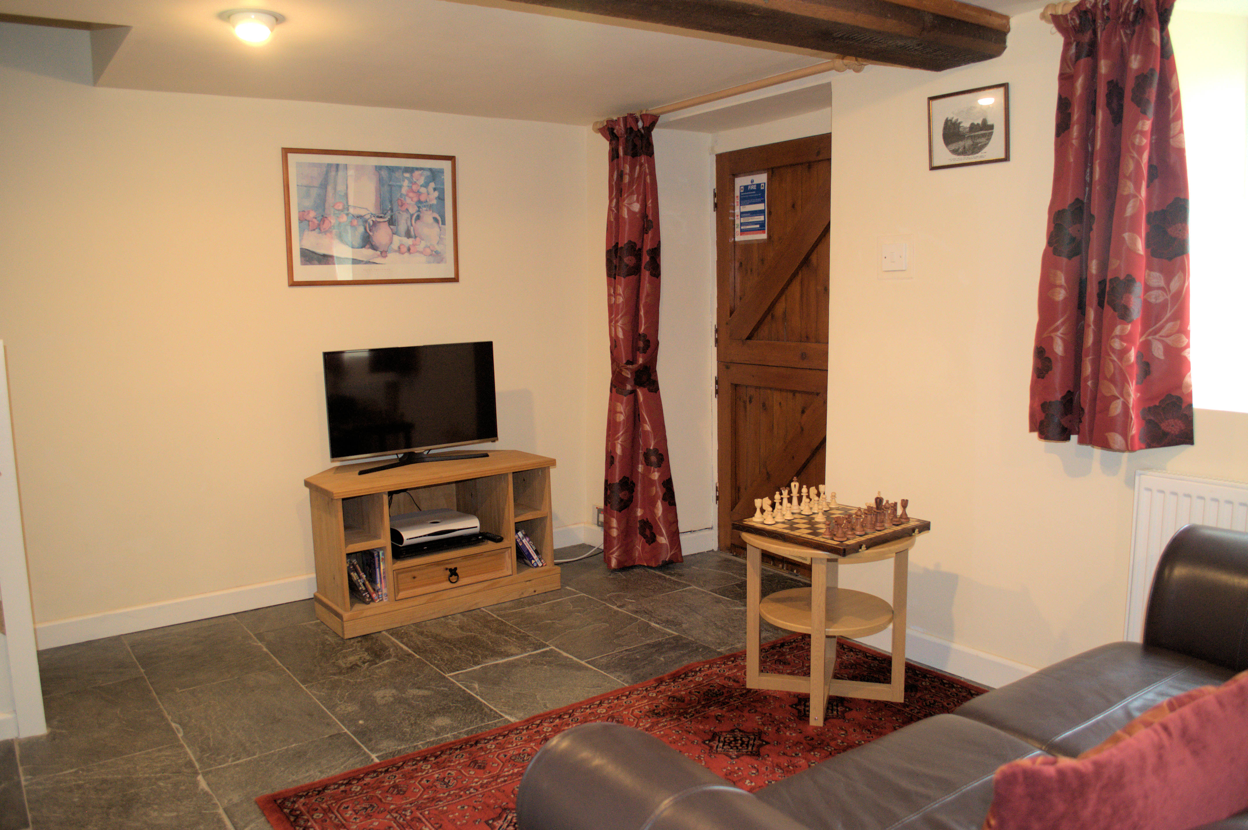 Upstairs in Severn Cottage showing a comfy leather sofa and roof window.
