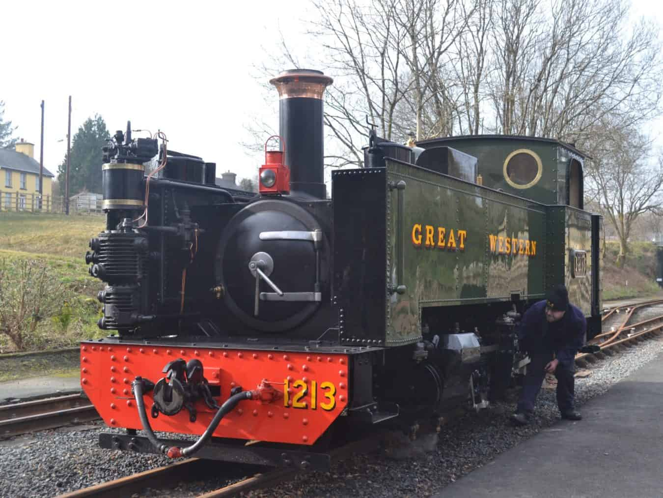 A narrow gauge steam engine being tended by the driver